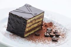 Schokoladenkuchen mit Kaffeebohnen auf weißer Platte, Süßspeise, Konditorei, Shop, Kakaopulver Stockbild