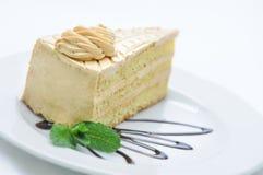 Schokoladenkuchen mit Kaffeebohnen auf weißer Platte, Süßspeise, Konditorei, Shop, Kakaopulver Stockfotos