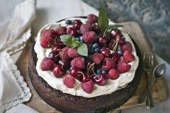 Schokoladenkuchen mit mascarpone auf rustikalem Hintergrund mit Himbeeren, Kirschen, Blaubeeren und tadellosen Blättern stockfotografie