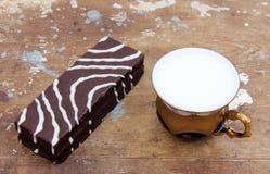 Schokoladenkuchen mit Schale Milch Stockfotos