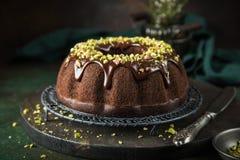 Schokoladenkuchen mit Schokoladenglasur und -pistazien lizenzfreies stockfoto