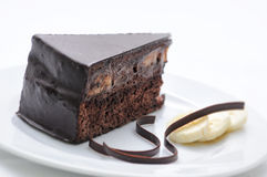 Schokoladenkuchen mit Strudeln auf weißer Platte, Konditorei, Fotografie für Shop, Süßspeise, Lizenzfreies Stockfoto