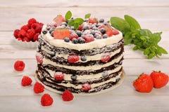 Schokoladenkuchen mit weißer Creme und frischen Früchten Stockfoto