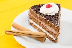 Schokoladenkuchen mit Zimt auf einem gelben hölzernen Tabellenhintergrund Stockfotografie