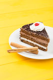 Schokoladenkuchen mit Zimt auf einem gelben hölzernen Tabellenhintergrund Stockbild