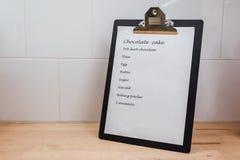 Schokoladenkuchen-Rezept-Klippbrett auf dem Tisch an der Küche Stockfotos