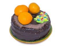 Schokoladenkuchen und -orangen auf einem keramischen Teller auf weißem Hintergrund Stockfoto