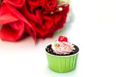 Schokoladenkuchen und -rosen auf weißem Hintergrund Lizenzfreie Stockfotografie