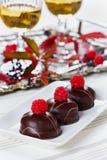 Schokoladenkuchen verziert mit Himbeeren in der weißen Platte mit Gläsern Weißwein Stockbild