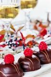 Schokoladenkuchen verziert mit Himbeeren in der weißen Platte mit Gläsern Weißwein Stockbilder