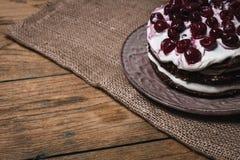 Schokoladenkuchenkuchen mit Grundkirsche auf einem hölzernen Brett Lizenzfreie Stockbilder