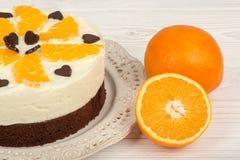 Schokoladenkuchenkuchen mit Sahne und Orangen auf dem weißen hölzernen Hintergrund Lizenzfreie Stockfotos
