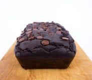 Schokoladenkuchenlaib der roten Bohne mit Schokoladensplittern auf hölzernem Schneidebrett Stockbild