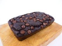 Schokoladenkuchenlaib der roten Bohne mit Schokoladensplittern auf hölzernem Schneidebrett Stockfotos