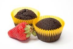 Schokoladenkuchenmuffins und -erdbeere auf weißem Hintergrund Stockfoto