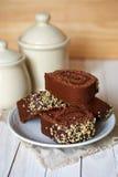 Schokoladenkuchenrolle auf einer weißen Untertasse Stockbild