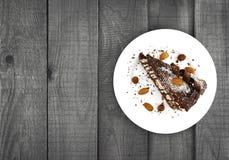 Schokoladenkuchenscheibe mit Nuss auf Platte auf Holztisch, Draufsicht Stockfotos