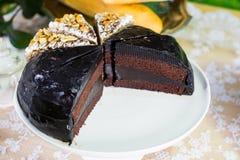 Schokoladenkuchenschnitt in einige Stücke mit anderem Kuchen auf Kuchenstand Lizenzfreie Stockbilder