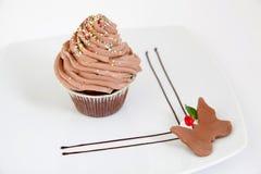Schokoladenmuffin mit dem Bereifen der Spitze und besprüht Stockfotos
