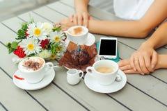 Schokoladenmuffin mit einer Kerze, Schalen mit Kaffee auf hölzernem Vorsprung Stockbilder