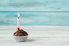 Schokoladenmuffin mit Kerze auf Holztisch gegen blauen Hintergrund Lizenzfreie Stockfotografie