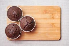 Schokoladenmuffins auf dem hölzernen Schneidebrett, Textraum Stockbild