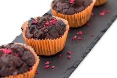 Schokoladenmuffins auf der Schieferplatte lokalisiert auf Weiß Lizenzfreie Stockfotos