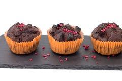Schokoladenmuffins auf der Schieferplatte lokalisiert auf Weiß Lizenzfreies Stockfoto