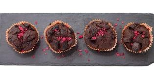 Schokoladenmuffins auf der Schieferplatte lokalisiert auf Weiß Stockfotos
