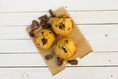 Schokoladenmuffins auf einem weißen Holztisch lizenzfreie stockfotografie
