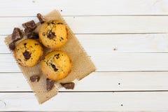 Schokoladenmuffins auf einem weißen Holztisch lizenzfreie stockbilder