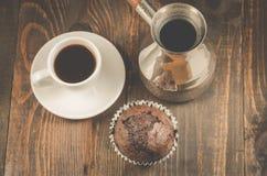 Schokoladenmuffins, Kaffeetasse und Türken/Schokoladenmuffins, Kaffeetasse und Türken auf einer hölzernen dunklen Tabelle, Draufs stockfotos