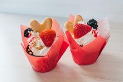 Schokoladenmuffins mit Erdbeeren und Blackberry-Beeren und süße Creme Selbst gemachte kleine Kuchen stockfotos
