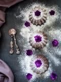 Schokoladenmuffins mit Puderzucker, violette Blumen, selektiver Fokus dunkel lizenzfreie stockbilder