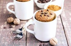 Schokoladenmuffins mit Schokoladenplätzchen dienten in den weißen Bechern lizenzfreies stockbild