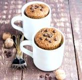 Schokoladenmuffins mit Schokoladenplätzchen dienten in den weißen Bechern lizenzfreie stockfotos