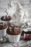 Schokoladenmuffins und keramische Santa Claus auf einer hellen Holzoberfläche Stockfotos