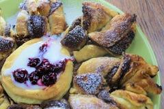 Schokoladennugget-Blätterteigblume mit der Vanillesoße und der Sauerkirsche bedeckt mit Puderzucker-, Grünem und Braunemhölzernem lizenzfreie stockfotografie