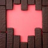Schokoladenoblaten werden in Form von Herzen auf einer Rotrückseite ausgebreitet Lizenzfreie Stockfotos