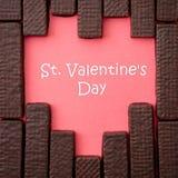 Schokoladenoblaten werden in Form von Herzen auf einer Rotrückseite ausgebreitet Lizenzfreies Stockfoto