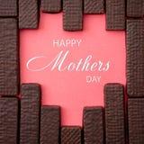 Schokoladenoblaten werden in Form von Herzen auf einer Rotrückseite ausgebreitet Stockfoto