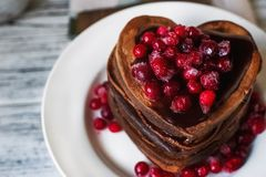 Schokoladenpfannkuchen in Form des Herzens, gegossen mit Schokoladenzuckerglasur und roten gefrorenen Moosbeeren auf einer weißen Lizenzfreies Stockbild