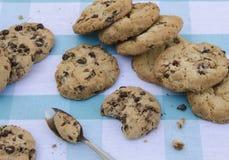 Schokoladenplätzchen auf einem Holztisch Schokoladensplitterplätzchen schossen auf einer blauen Tischdecke, Nahaufnahme Lizenzfreies Stockfoto