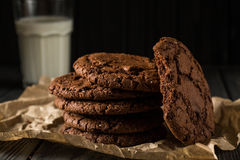 Schokoladenplätzchen auf Kraftpapier mit Glas Milch Lizenzfreies Stockfoto