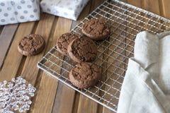 Schokoladenplätzchen am Metallgrill, mit Serviette und Geschenk auf hölzernem Hintergrund lizenzfreie stockfotografie