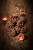 Schokoladenplätzchen mit Schokolade auf einem hölzernen Hintergrund mit Kerzen 1 Lizenzfreies Stockfoto