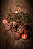 Schokoladenplätzchen mit Tannenzweigen auf einem hölzernen Hintergrund mit Kerzen 1 Stockbild