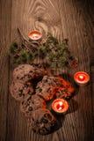 Schokoladenplätzchen mit Tannenzweigen auf einem hölzernen Hintergrund mit Kerzen 1 Stockfotografie