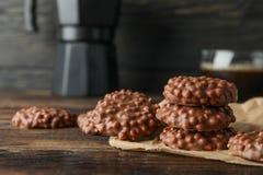 Schokoladenplätzchen und -Tasse Kaffee auf Holztisch gegen dunklen Hintergrund stockfoto