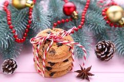 Schokoladenplätzchen und Weihnachtsdekoration auf rosa hölzernem Hintergrund stockfotografie